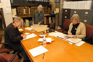 VOLUNTEER researchers, left to right, Carol Damerval, Rodi Lee, and Ellen Osborn look at historical records at the El Dorado County Historical Museum recently. Democrat photo by Pat Dollins